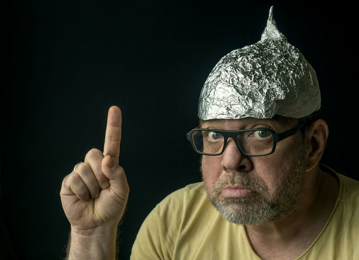 Strange man in a foil cap on his head. conspirology concept