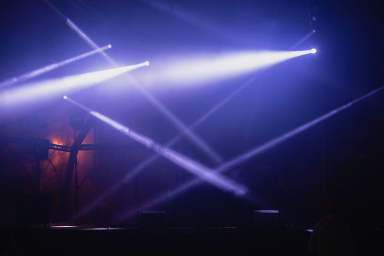 Light beams on a empty stage against dark background Stage Stage - Performance Space Arts Culture And Entertainment Lighting Equipment Illuminated Performance Light Beam Nightlife Spotlight Light Laser Dark Event Stage Light Festival Bright Popular Music Concert Projection