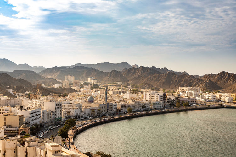 View to the corniche in Muscat, Oman. Architecture Built Structure Building Exterior Mountain City Water Sky Cloud - Sky Nature Building Mountain Range Residential District Cityscape No People Day Travel Destinations High Angle View Outdoors Transportation Bay