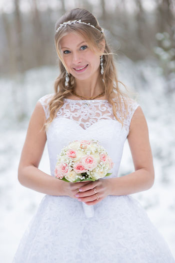 Portrait of bride standing on field during winter