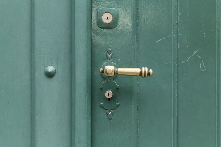 Close-up of a green painted wooden door with a brass handle and two key holes. Copy Space Green Green Color Painted Backgrounds Brass Close-up Design Detail Door Doorknob Entrance Full Frame Green Color Handle Keyhole Knob Lock Metal No People Protection Retro Styled Security Wood - Material Wooden