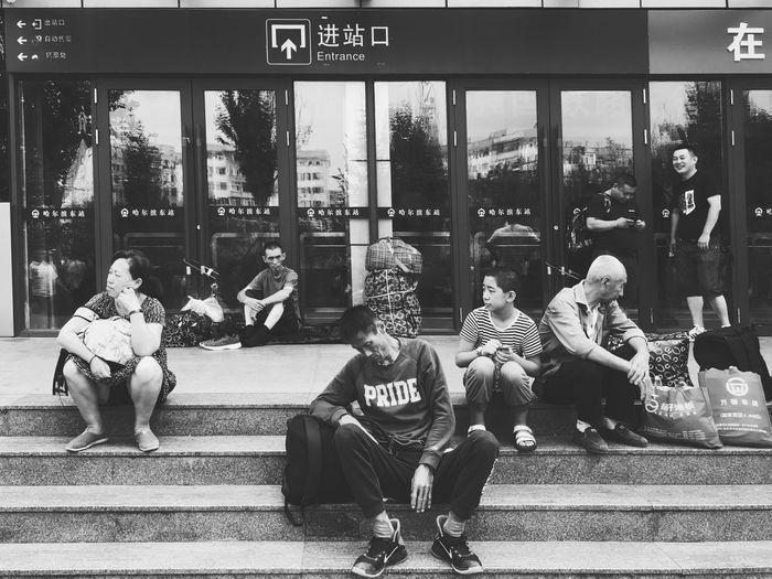 疲惫 Real People Men Group Of People People Sitting Text Day Architecture Outdoors Full Length Built Structure Leisure Activity Lifestyles Casual Clothing Relaxation City Western Script Representation Communication Adult