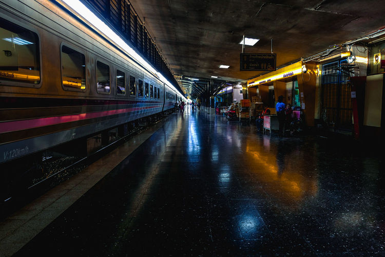 Train on railroad station platform at night