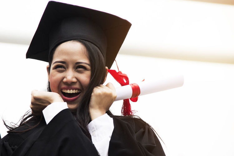 Cheerful young woman in graduation gown