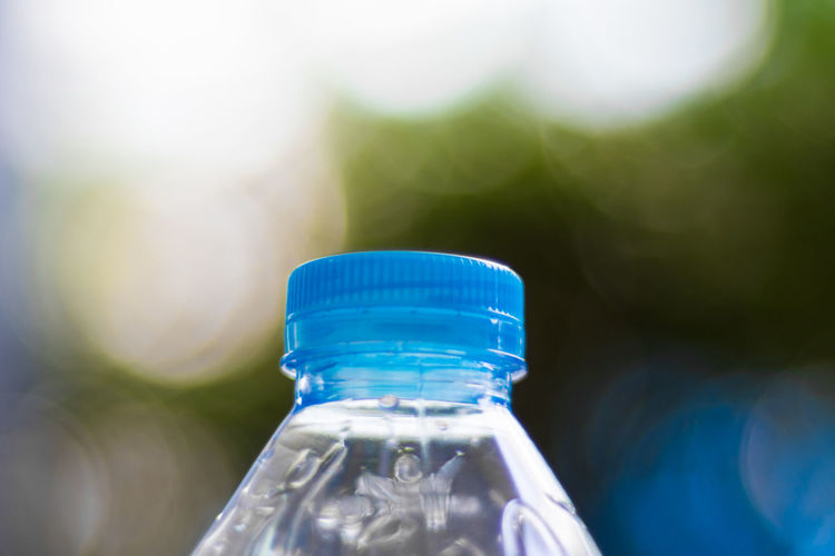 Close-up of cropped water bottle against blurred background