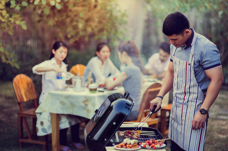 Barbecue Barbecue Grill Casual Clothing Day Focus On Foreground Food Food And Drink Group Of People Leisure Activity Lifestyles Men Outdoors People Preparing Food Real People Standing Table Togetherness Young Adult Young Men Young Women