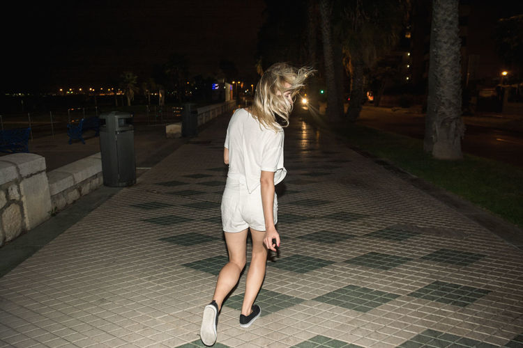 Rear view of woman running on footpath at night