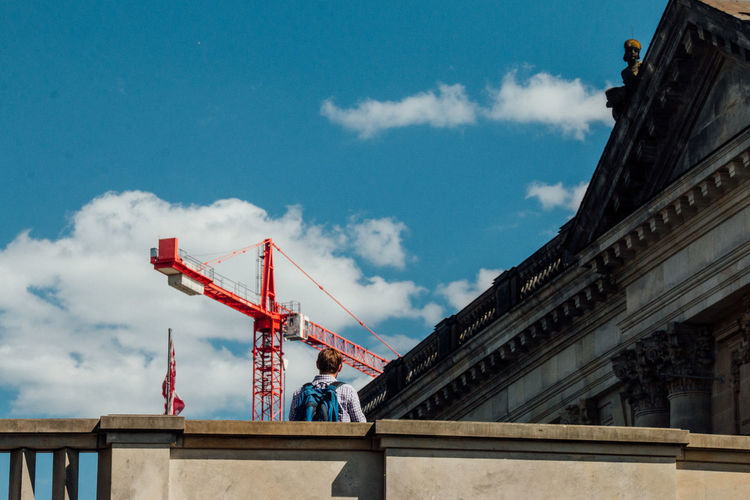 Rear View Of Man Standing By Historic Building Against Crane
