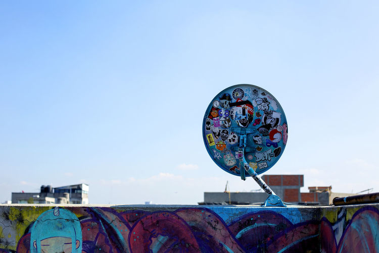 Low angle view of graffiti on metal against sky