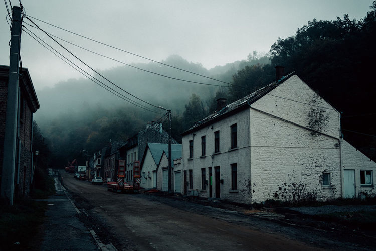 Ardennes Atmospheric Mood darkness and light Dark Eerie Beautiful Ardennen Belgium Misty Morning Mist Abandoned Building Exterior Architecture Built Structure Building Sky House Residential District No People Cable Fog Nature Street Road Transportation City Electricity  Tree The Way Forward Direction Pollution Air Pollution