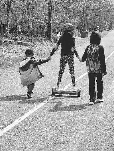 Rear view of kids walking on road