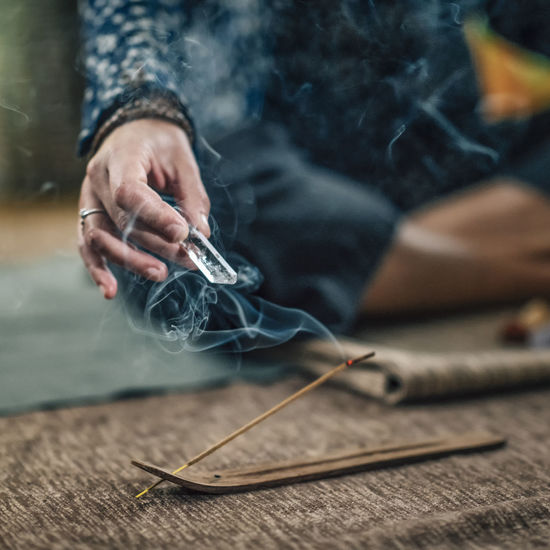 Close-up of hand holding incense stick