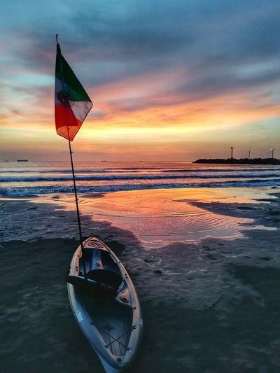Kayak at beach against sky during sunset
