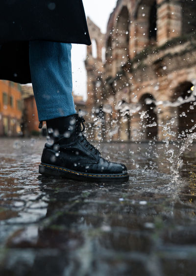 Low section of man standing on wet footpath