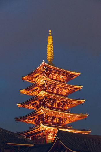 Illuminated temple against sky at dusk