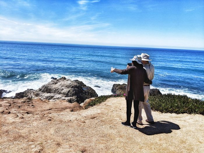 Couple taking smartphone selfie from Ocean's cliffs edge. Smartphone Selfie Couple Together Side By Side Cameraphone Hats Cliff's Edge Ocean Overlook Whale Watching Sandstone Background Nature Leisure Distance Tourist Young People Sideview Water Photography Themes Sea Men Camera - Photographic Equipment Digital Single-lens Reflex Camera Technology Full Length Photographing Camera Stay Out The Mobile Photographer - 2019 EyeEm Awards The Traveler - 2019 EyeEm Awards The Great Outdoors - 2019 EyeEm Awards