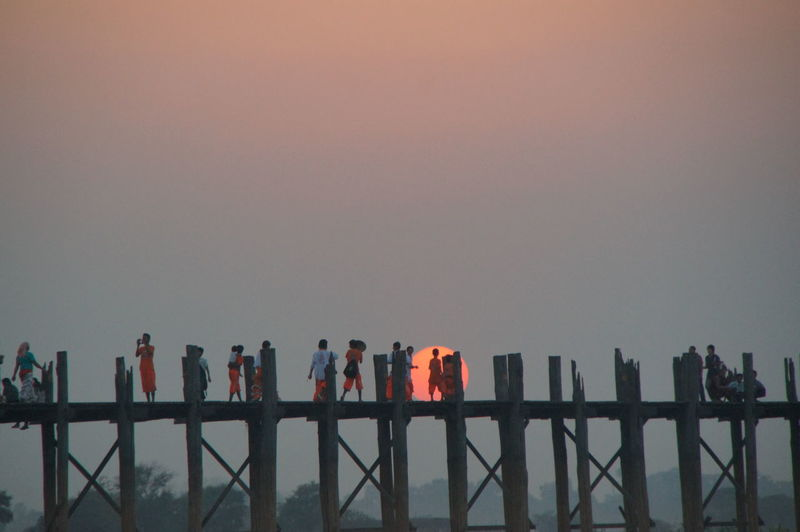 People standing by bridge during sunset