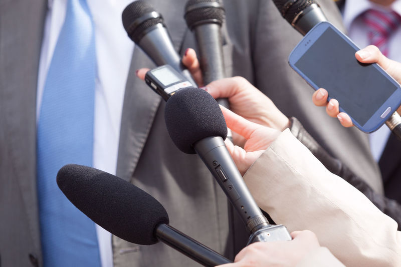 Cropped hand of journalist holding microphone in front of businessman