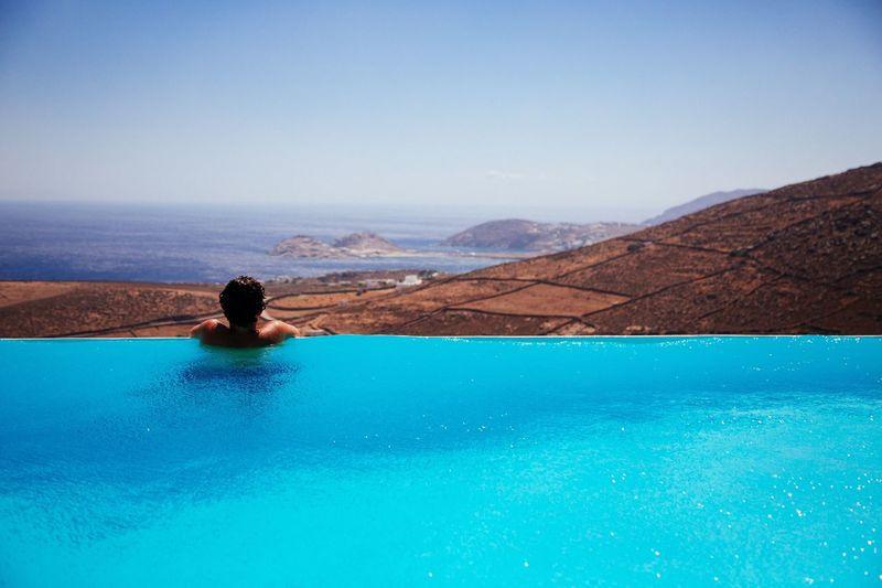 Man in swimming pool against blue sky