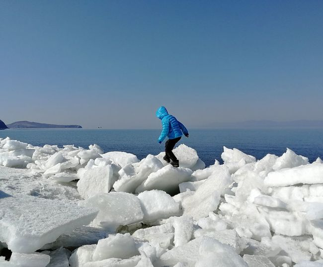 Girl walking on ice at beach