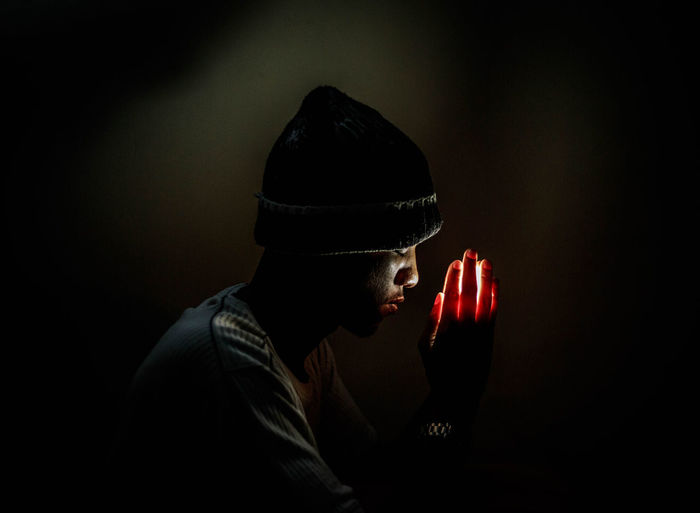 prayer in the dark Faith Hope Pray This Is Masculinity Black Background Close-up Headshot Illuminated Indoors  Lifestyles Men One Person People Real People Studio Shot Young Adult EyeEmNewHere The Creative - 2018 EyeEm Awards HUAWEI Photo Award: After Dark