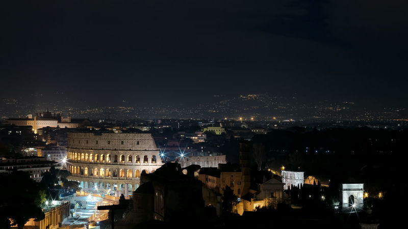 Panoramic night view of Rome. In the foreground the illuminated Colosseum, on the right the Arch of Constantine and the area of the Imperial forums with the Arch of Titus Building Exterior Night City Architecture Illuminated Built Structure Cityscape Building Residential District No People Sky Nature City Life High Angle View Copy Space Outdoors Community Travel Destinations Skyscraper Coliseum Rome Nightphotography Night Lights