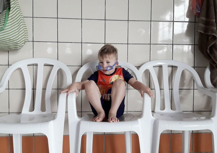 Full length of boy sitting on chair at home