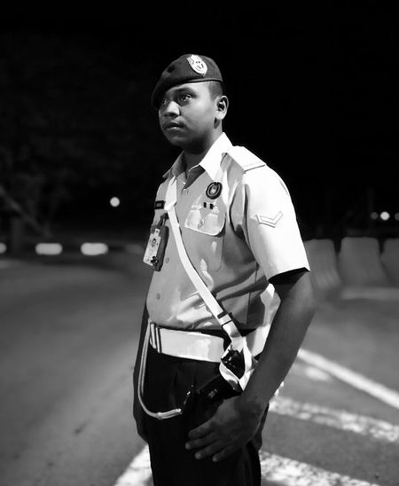 Police man looking away while standing on road at night