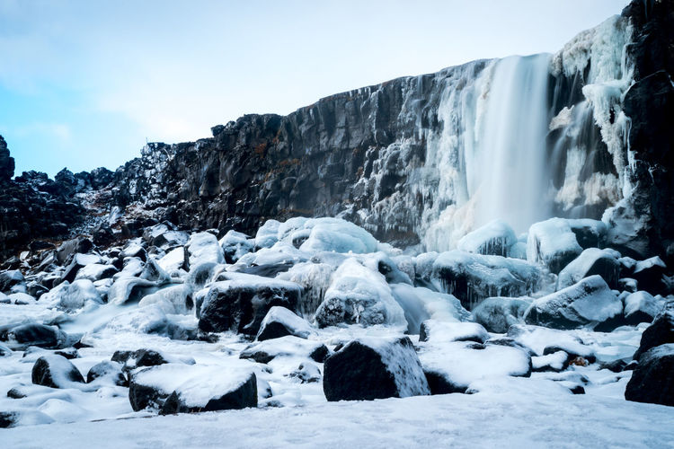 A long exposure of a waterfall in the snow covered hills at a thingvellir national park in iceland