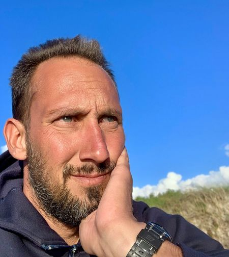 Close-up of thoughtful mature man against blue sky