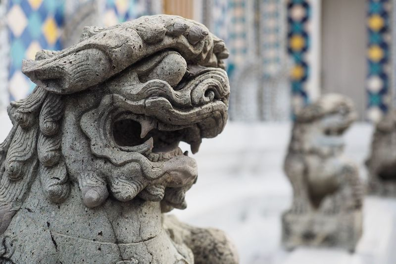 Concrete Chinese styled lion on foreground and the out of focus one on background. EyeEm Selects Art And Craft Representation Sculpture Statue Focus On Foreground Creativity Craft No People Religion Belief Close-up Spirituality Day