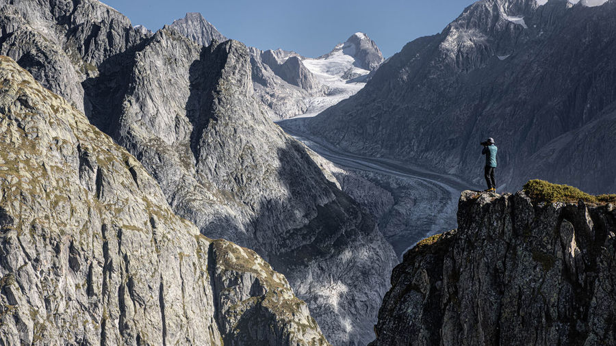 Man standing on rock by mountain