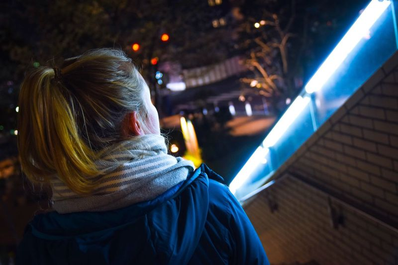 Rear view of woman with ponytail walking by illuminated wall at night