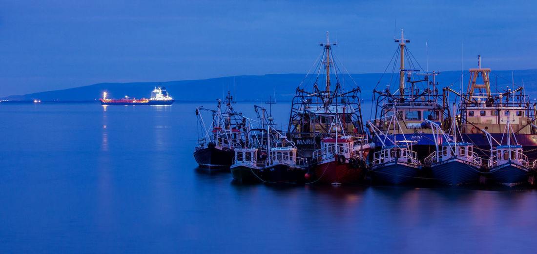 Boats moored at harbor against sky at dusk