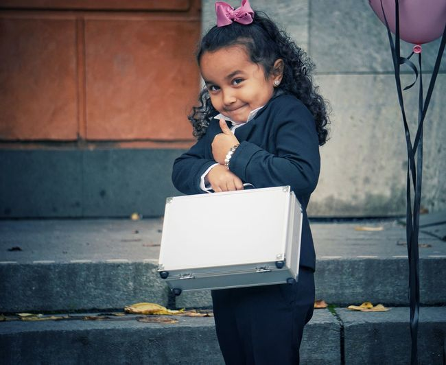 Portrait of cute girl holding briefcase while gesturing on staircase