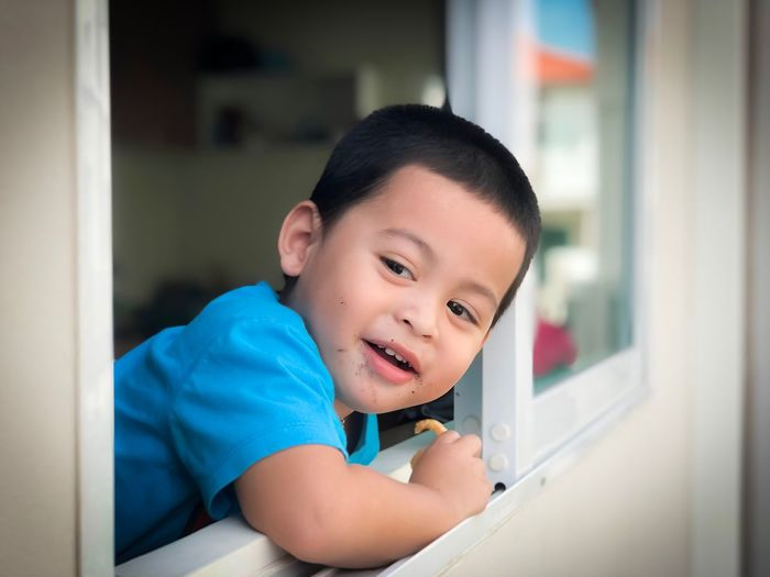Smiling boy looking through window while standing at home