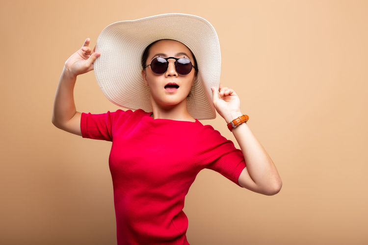 Portrait of woman wearing hat and sunglasses while standing against brown background