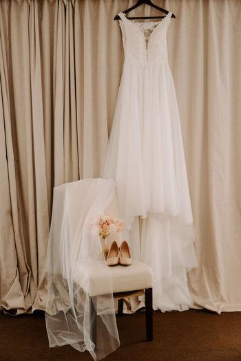 Wedding dress hanging on coat hanger against brown curtain
