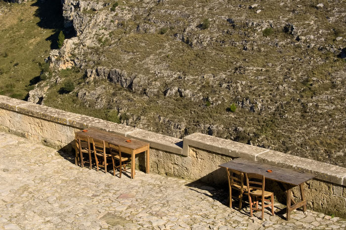 Old wooden tables and chairs overlooking the canyon of the sassi or stones of Matera European capital of culture 2019, Basilicata, Italy Day Nature Architecture Outdoors Matera Basilicata Italy Sassi Di Matera Capital Of Culture 2019 Wooden Table Old Ancient Hystorical Heritage Typical Traditional Canyon Chair View Panorama Wildlife History South Rocks