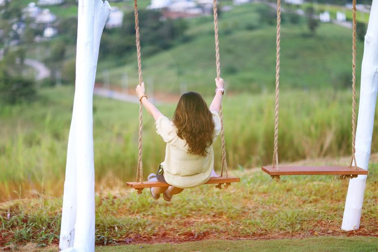 Rear view of woman on swing at playground