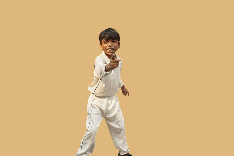 Portrait of happy boy standing against orange background