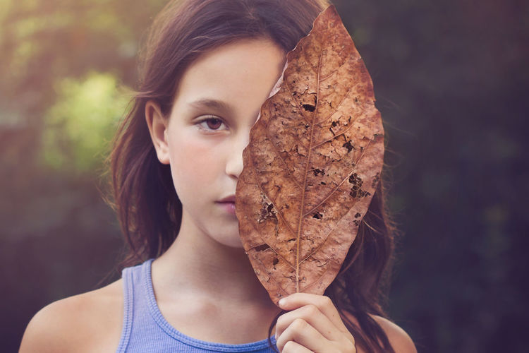 Close-up portrait of cute beautiful girl holding dry leaf in park