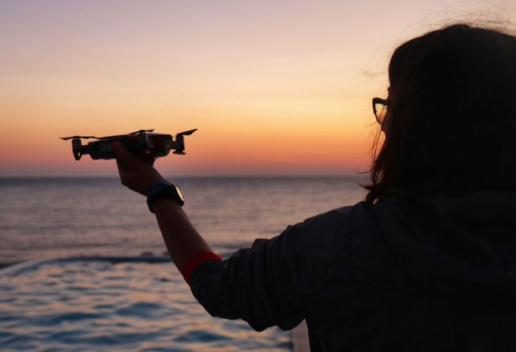 Rear View Of Woman Holding Drone At Beach Against Sky During Sunset
