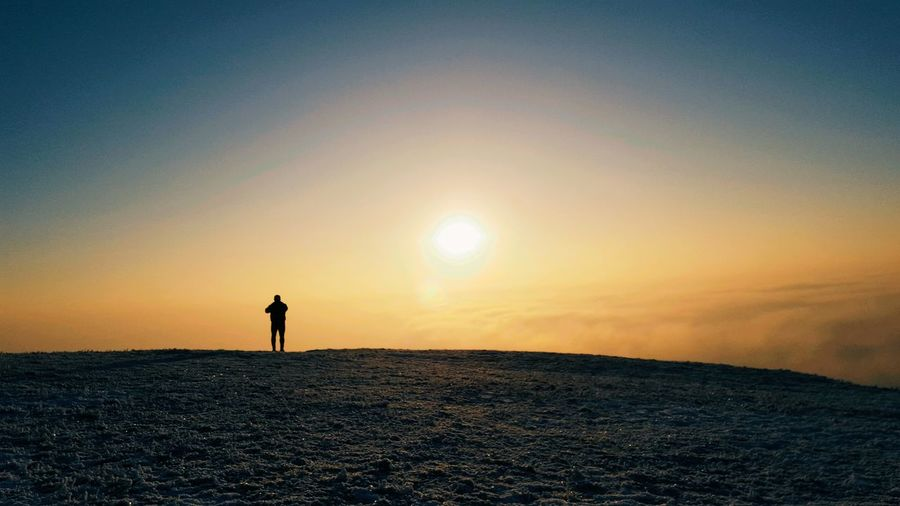 Silhouette Of Man Standing On Field Against Sky During Sunset