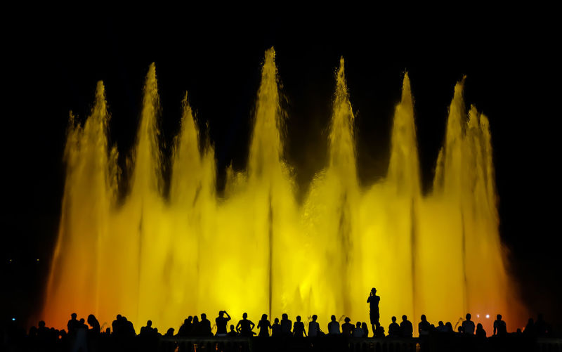 Silhouette Of People At Night In Front Of A Fountain