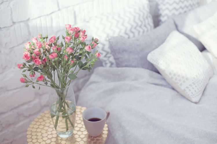 Flower Vase And Coffee On Table By Bed At Home