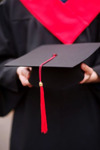 Midsection Of Male University Student Holding Mortarboard