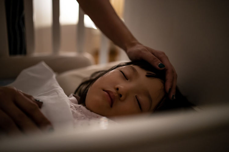 Close-up of mother hand touching sleeping girl on bed