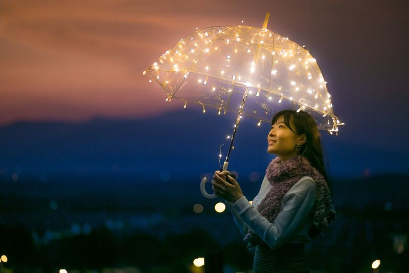 Smiling young woman holding illuminated umbrella against sky at dusk