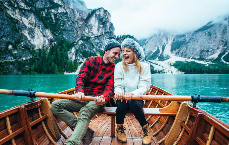 Young couple sitting on boat against mountains